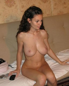 Naked brunette with nice huge tits on a wide bed