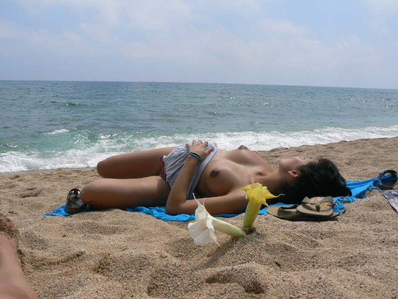 Pregnant with girlfriend relaxing topless on the beach 1 photo