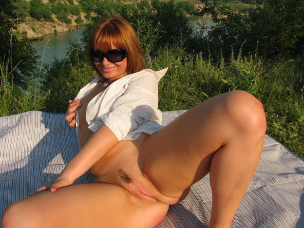 Cute redhead lady shows pussy under skirt at the lake 11 photo