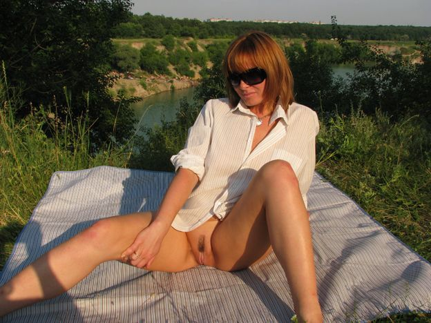 Cute redhead lady shows pussy under skirt at the lake 13 photo