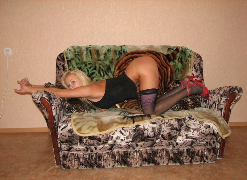 Playful bitch with narrow pussy spreads long legs on a sofa 3 photo