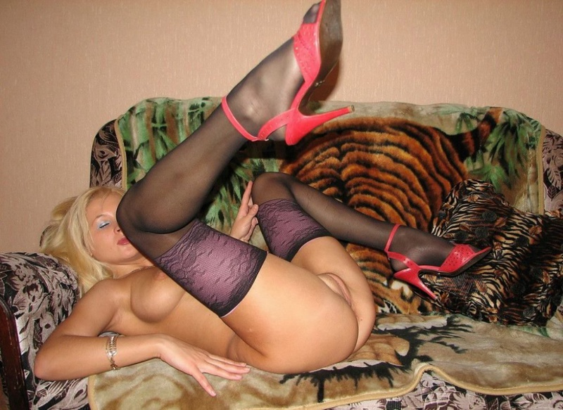 Playful bitch with narrow pussy spreads long legs on a sofa 9 photo