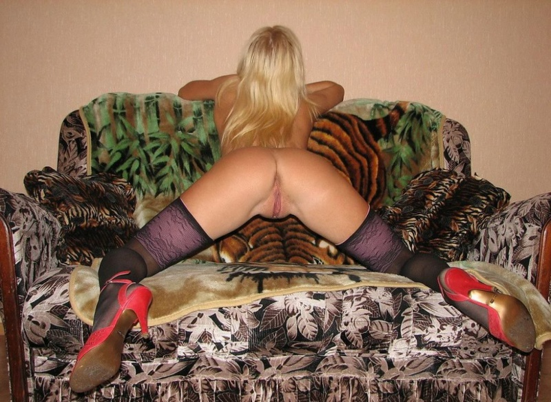 Playful bitch with narrow pussy spreads long legs on a sofa 8 photo