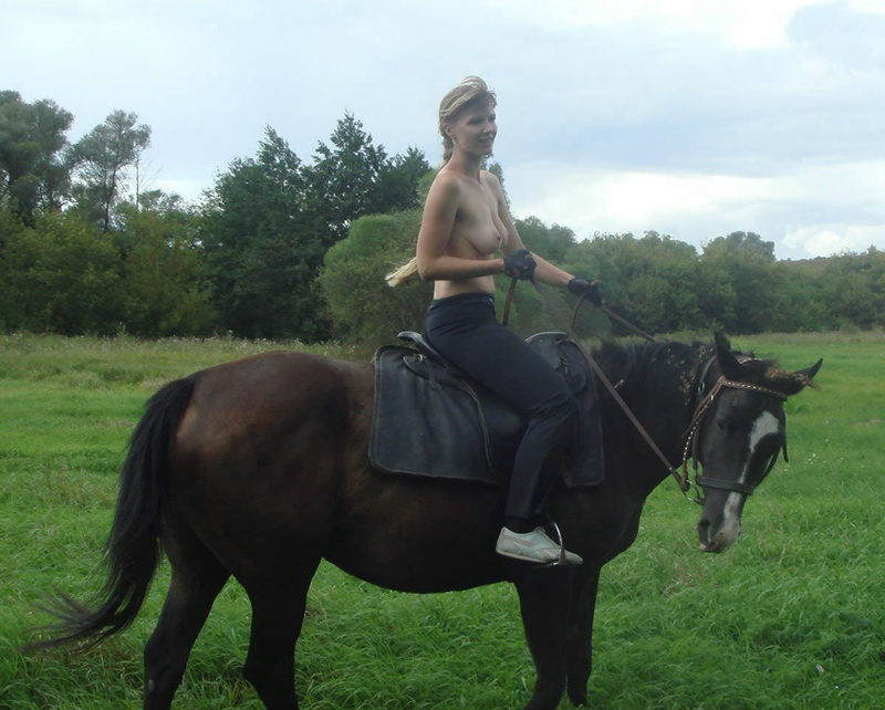 Girl posing topless on a horse among the field 5 photo