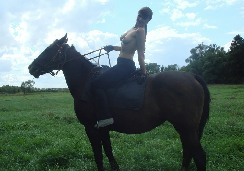 Girl posing topless on a horse among the field 12 photo