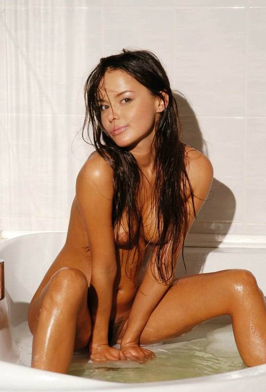Tanned brown-eyed beauty is bathed in the tub 1 photo