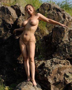 Mature babe with tender pink pussy posing on a rocky cliff