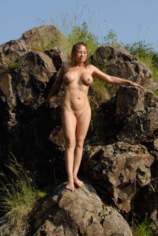 Mature babe with tender pink pussy posing on a rocky cliff 8 photo