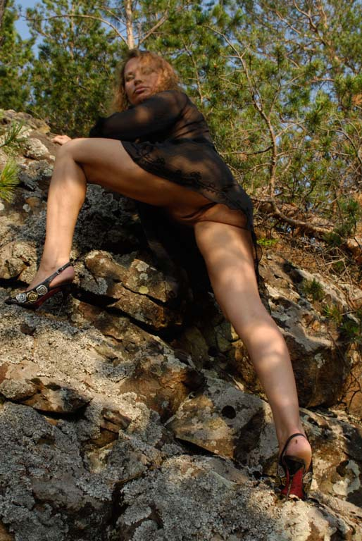 Mature babe with tender pink pussy posing on a rocky cliff 3 photo