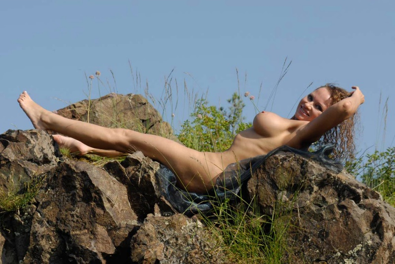 Mature babe with tender pink pussy posing on a rocky cliff 11 photo