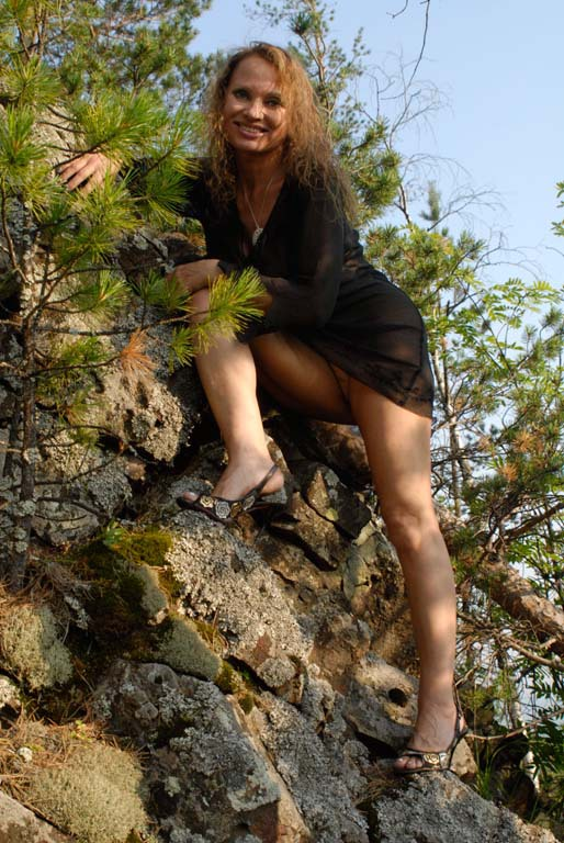 Mature babe with tender pink pussy posing on a rocky cliff 5 photo