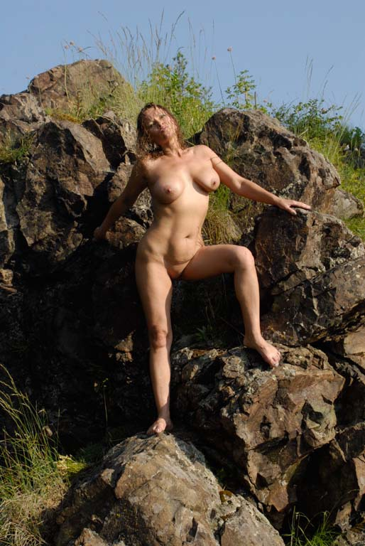 Mature babe with tender pink pussy posing on a rocky cliff 9 photo