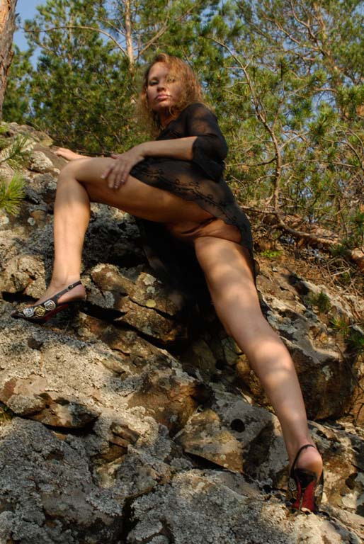 Mature babe with tender pink pussy posing on a rocky cliff 4 photo