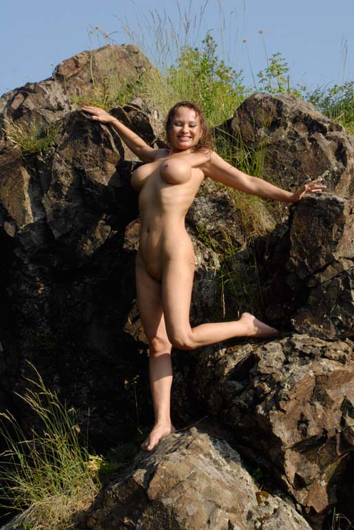 Mature babe with tender pink pussy posing on a rocky cliff 10 photo