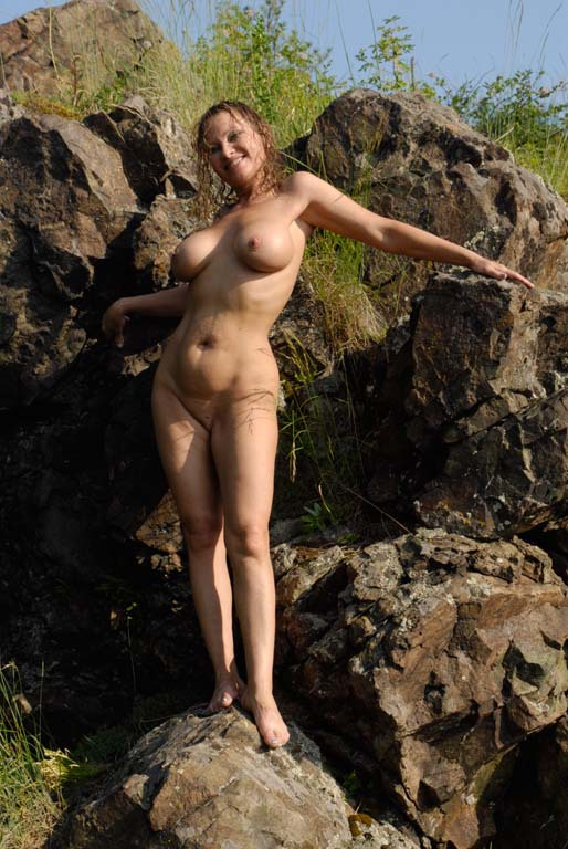 Mature babe with tender pink pussy posing on a rocky cliff 7 photo