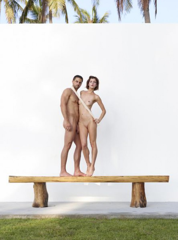 Beautiful couple posing nude on the big wooden bench 1 photo