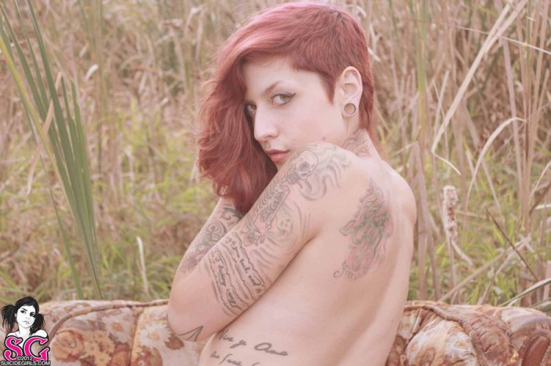 Redhead lusty babe in a tattoo posing on country meadow 4 photo