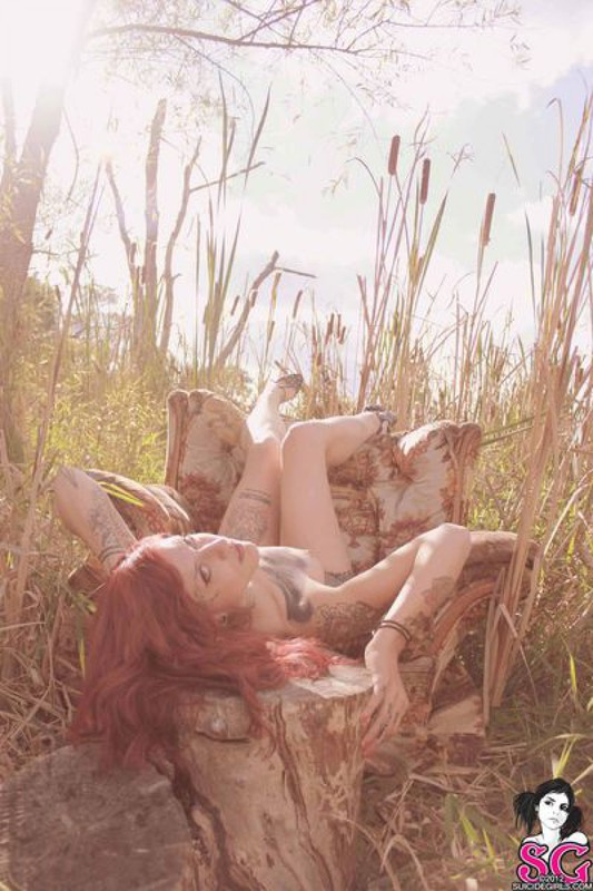 Redhead lusty babe in a tattoo posing on country meadow 11 photo