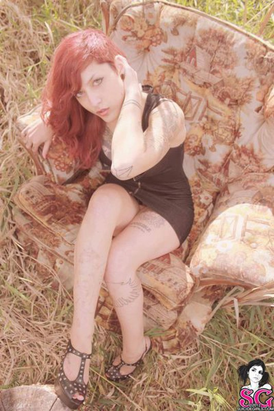 Redhead lusty babe in a tattoo posing on country meadow 18 photo