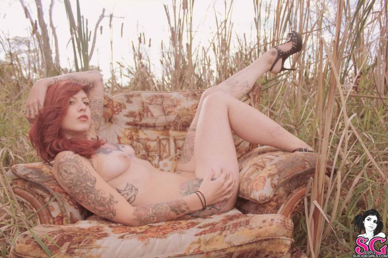 Redhead lusty babe in a tattoo posing on country meadow 32 photo