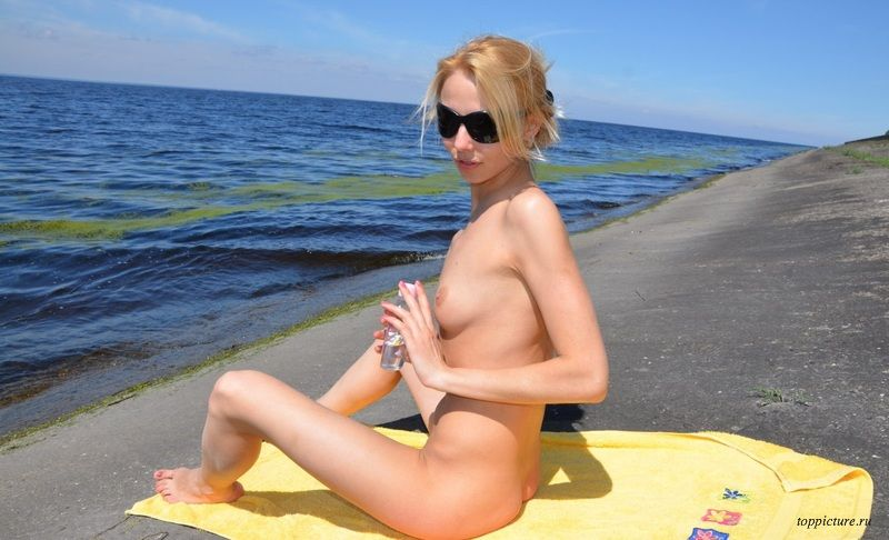 Uninhibited girl in sunglasses sunbathing naked on the beach 8 photo