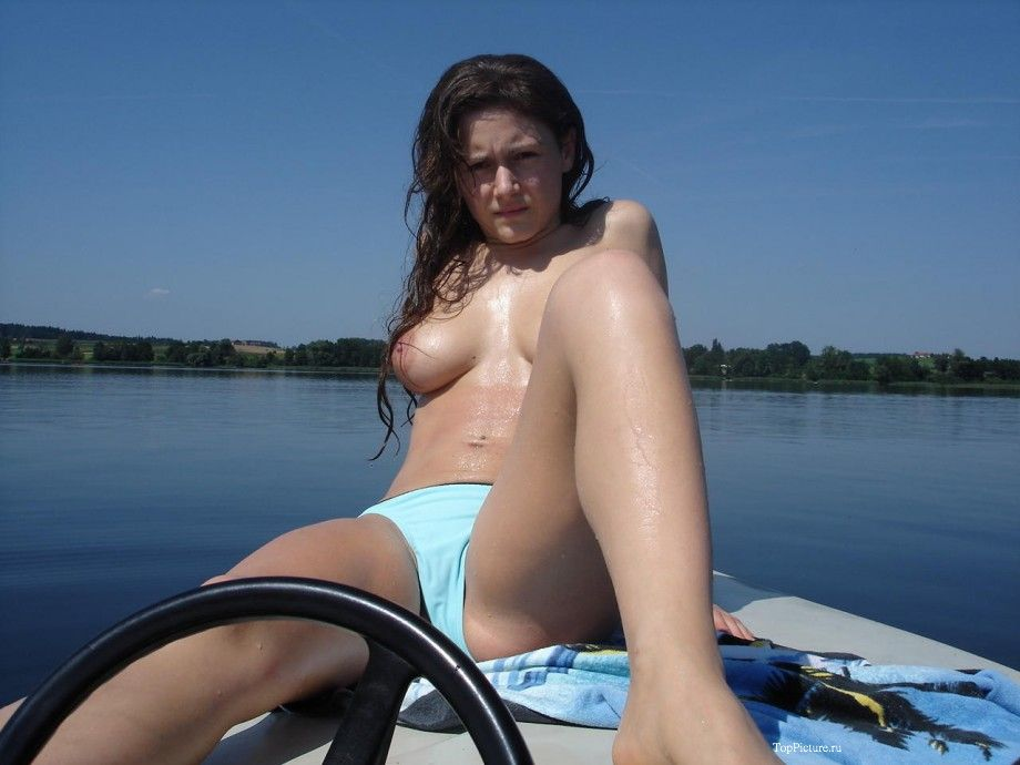 Girlfriend with big boobs rides on the river on a boat topless 10 photo