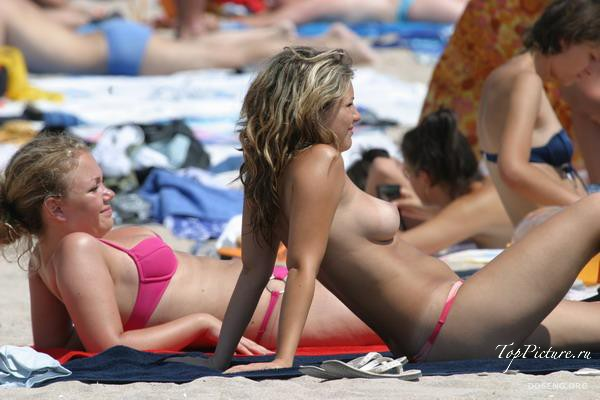 Girls sunbathing and swimming topless on the beach 34 photo