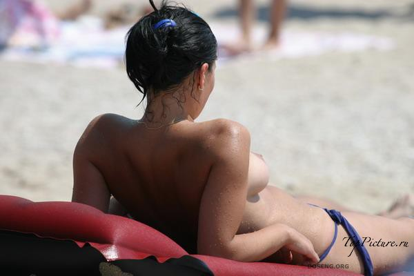 Girls sunbathing and swimming topless on the beach 35 photo